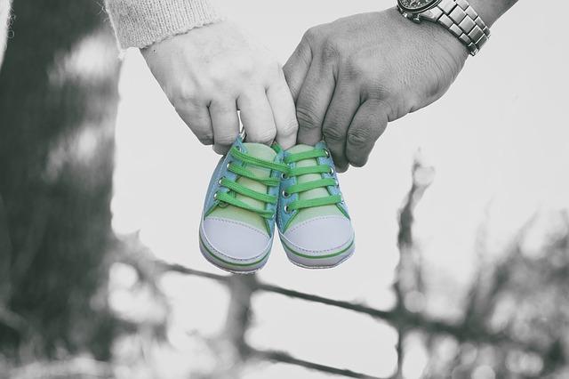 Dos manos de hombre y mujer sosteniendo unas zapatillas de bebé